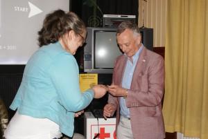 Museiföreståndare Elin Andersson ger Roland Palmqvist en optimistnål som tack för hans föreläsning om romers situation i Rumänien. BILD: MIKAEL HILDINGSSON